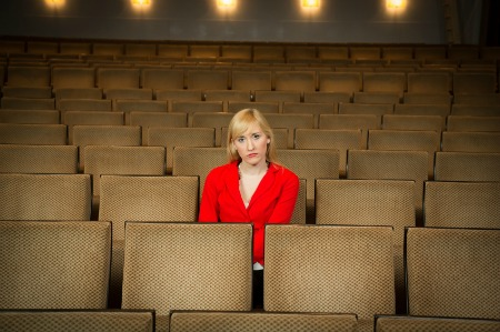 Single woman sitting lonely in an empty cinema or theatre